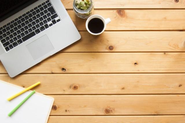 木のデスクにMacやコーヒーが入ったカップが乗っている画像.alt
