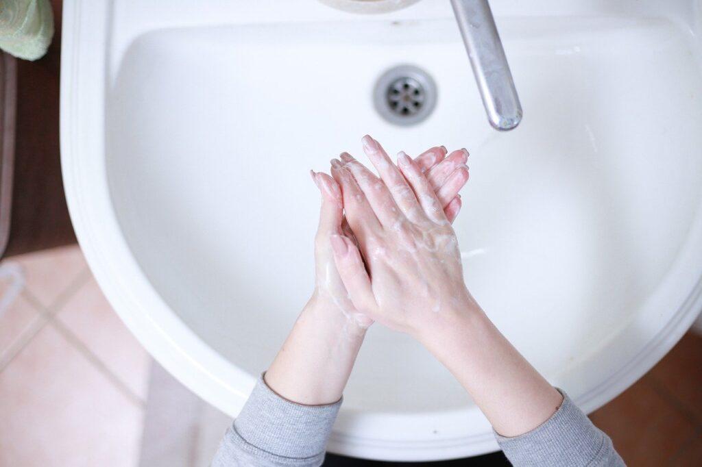 女性が洗面所で手を洗っている写真.alt