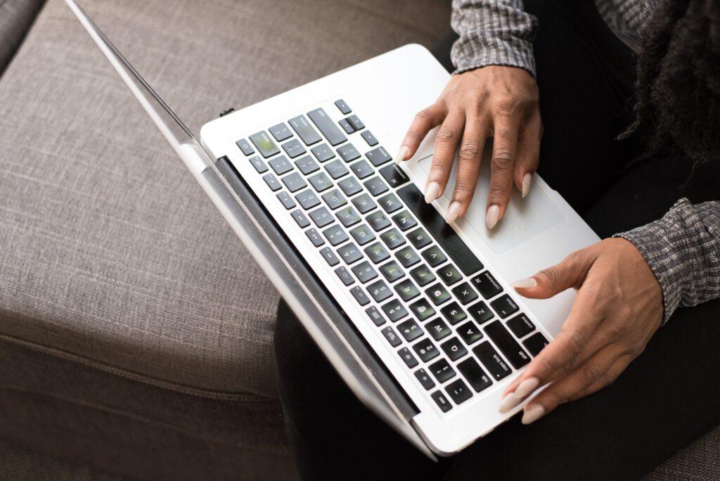 ソファの上で膝の上にパソコンを起きながら操作する男性の写真.alt