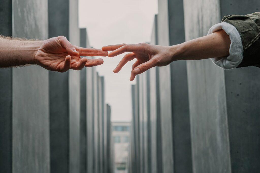 離れている手を触ろうとしている写真.alt